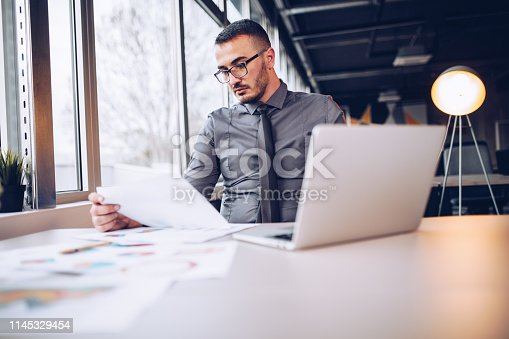921587490 istock photo Portrait of young successful businessman sitting at his desk in the office. 1145329454