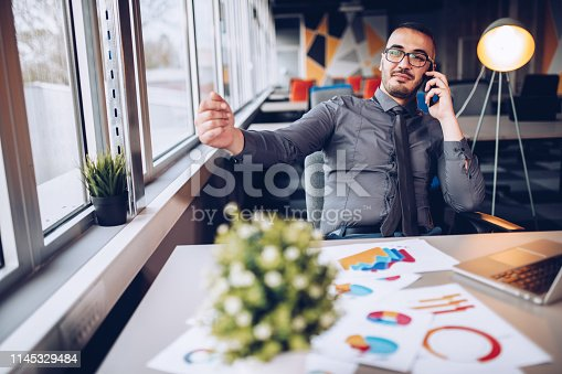 921587490 istock photo Portrait of young successful businessman sitting at his desk in the office. 1145329484