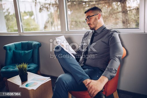 921587490 istock photo Portrait of young successful businessman sitting at his desk in the office. 1145387964