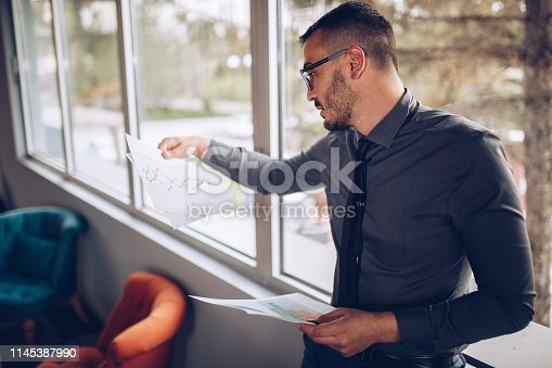 921587490 istock photo Portrait of young successful businessman sitting at his desk in the office. 1145387990