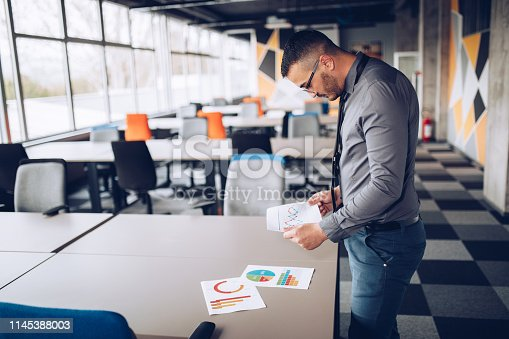921587490 istock photo Portrait of young successful businessman sitting at his desk in the office. 1145388003