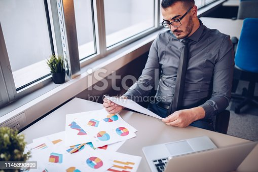 921587490 istock photo Portrait of young successful businessman sitting at his desk in the office. 1145390899