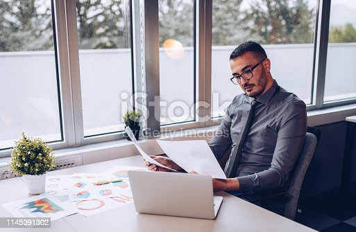 921587490 istock photo Portrait of young successful businessman sitting at his desk in the office. 1145391302