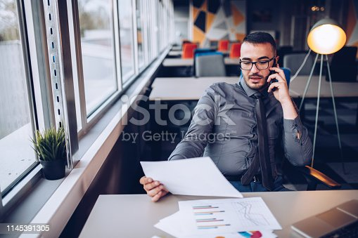 921587490 istock photo Portrait of young successful businessman sitting at his desk in the office. 1145391305