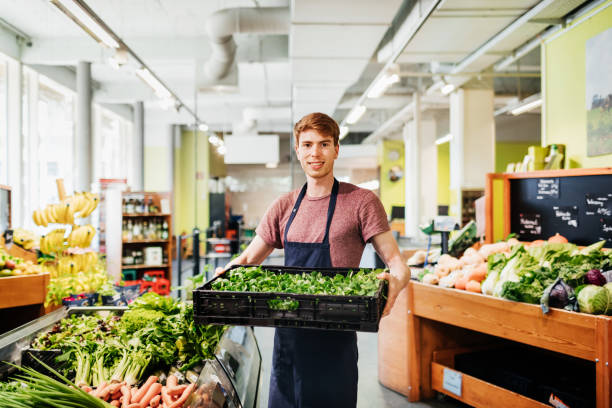 Porträt von jungen Supermarkt Clerk Holding Kiste von Gemüse – Foto