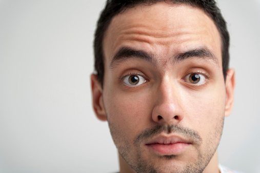 Portrait of young surprised brunet man with widely open eyes
