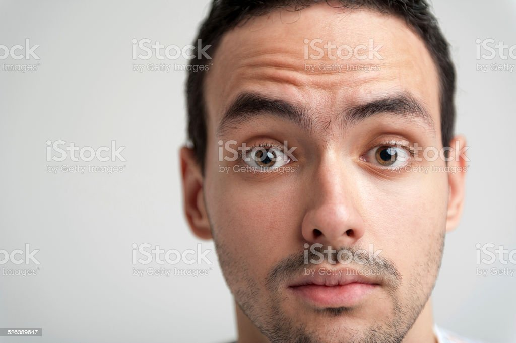 Portrait of young surprised brunet man with widely open eyes stock photo
