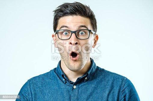 istock Portrait of young surprised man with opened mouth. Isolated on gray 835444332