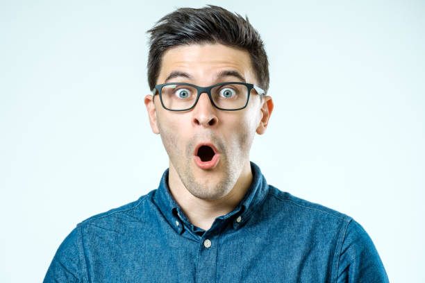 portrait of young surprised man with opened mouth. isolated on gray - astonishment stock photos and pictures