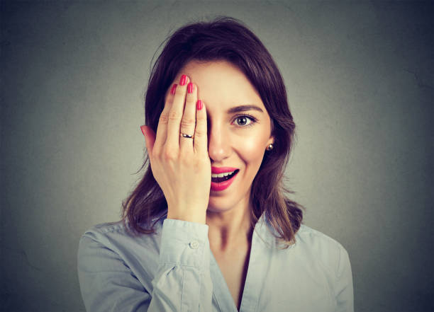 portrait of young surprised woman covering half face with her hand - omg stock photos and pictures