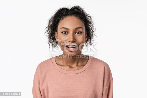 910856488 istock photo Portrait of young surprised woman with opened mouth standing isolated on white background 1199905871