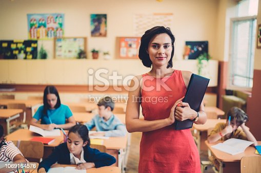 Schoolchildren studying in class and teacher looking at camera