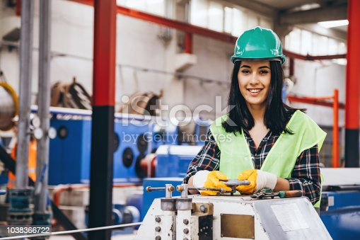 Portrait of a happy technician or engineer woman looking at camera and smiling while checking, opening or adjusting valve equipment in industrial site factory or utility.