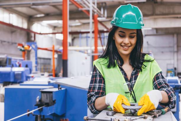 porträtt av ung tekniker kvinna som arbetar med ventiler i fabrik - kvinna ventilationssystem bildbanksfoton och bilder