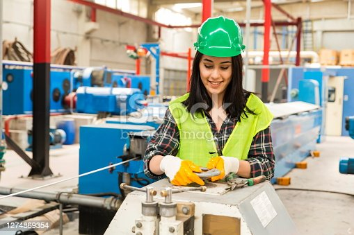 Portrait of a happy technician or engineer businesswoman checking, opening or adjusting valve equipment in industrial site factory or utility.