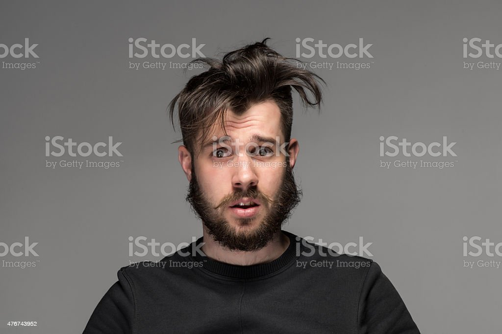 Portrait of young tousled man in studio stock photo