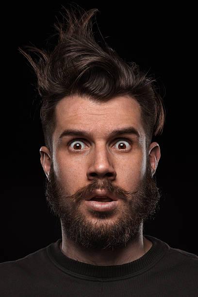 porträt der junge mann im studio, vom wind zerzaust - lustige augenbrauen stock-fotos und bilder