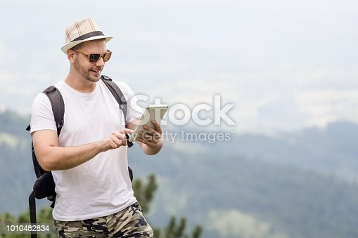 665586146istockphoto Portrait of young traveler with backpack holding and looking at digital tablet device. 1010482834