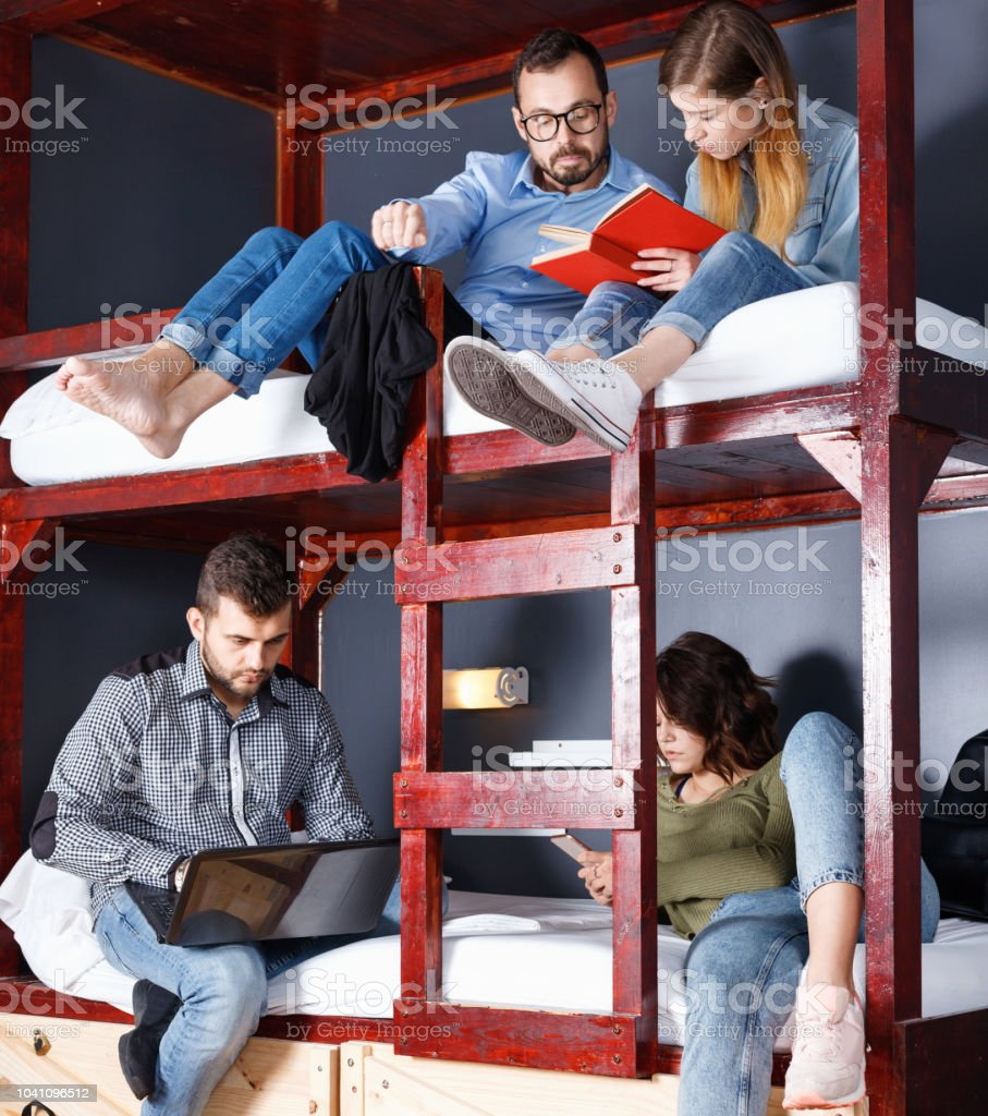 Portrait of young travelers communicating while resting in modern cozy hostel bedroom stock photo