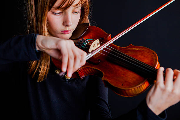 Portrait of young violinist with old and valuable violin.. stock photo