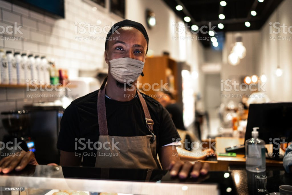 Portrait of young waiter with face mask in coffee shop Portrait of young waiter with face mask in coffee shop 20-24 Years Stock Photo