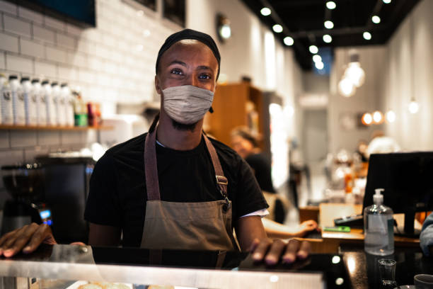 portrait of young waiter with face mask in coffee shop - small business owner stock pictures, royalty-free photos & images