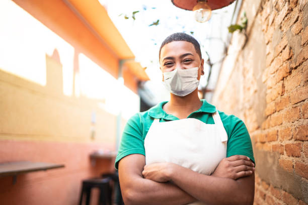 Portrait of young waitress working in a coffee shop using protective mask stock photo