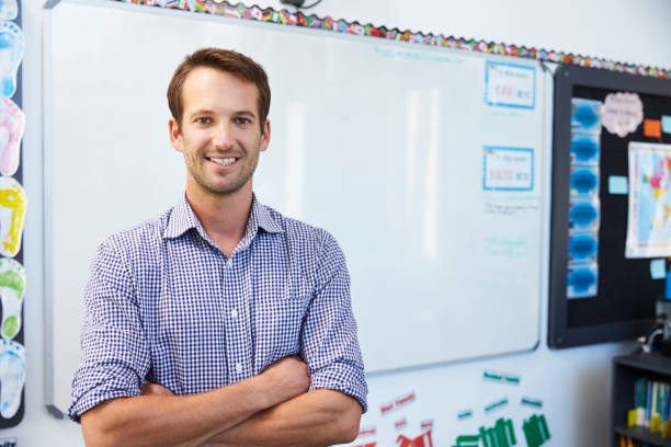 portrait of young white male teacher in school classroom - instructor stock photos and pictures