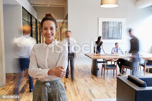 istock Portrait of young white woman in a busy modern workplace 904598344