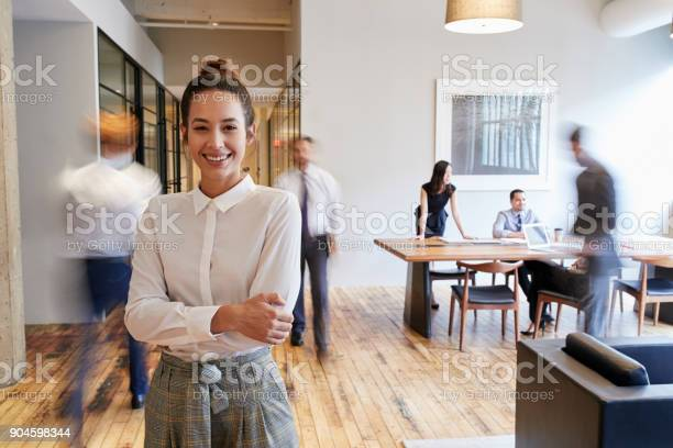 Portrait of young white woman in a busy modern workplace picture id904598344?b=1&k=6&m=904598344&s=612x612&h=psvzfadzr8t7xfhie6ajvntof8rhbvybthhgmpwb1ee=