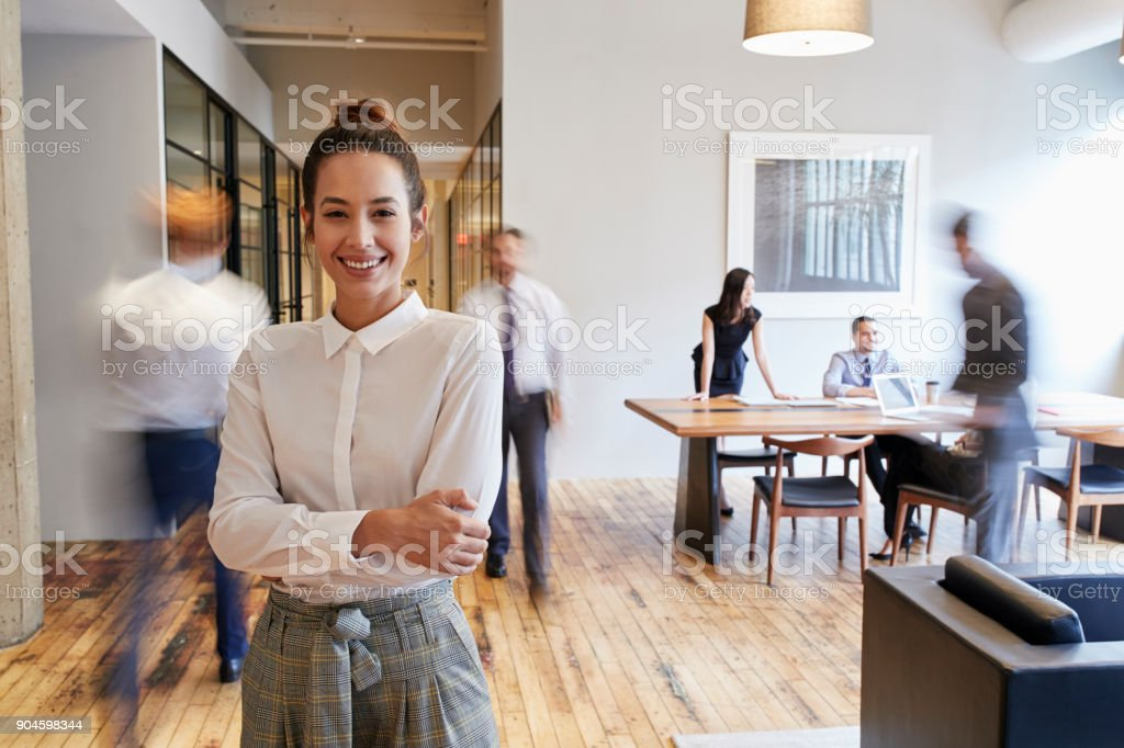 Portrait of young white woman in a busy modern workplace - foto stock