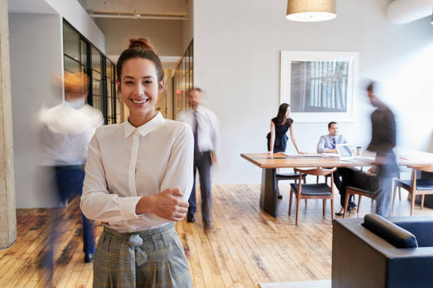 Portrait of young white woman in a busy modern workplace stock photo