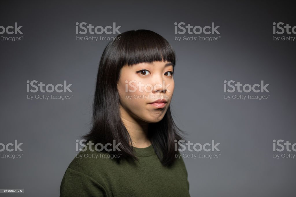 Portrait Of Young Woman Against Gray Background stock photo