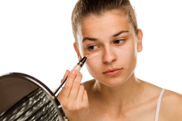 Portrait of young woman applying concealer with brush on white background stock photo
