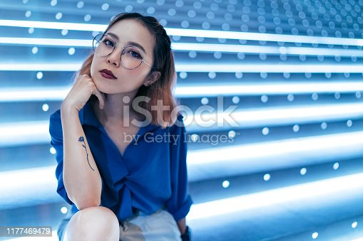 A portrait of young  and beautiful woman sitting in front of bright blue lights and looking at camera in confidence.