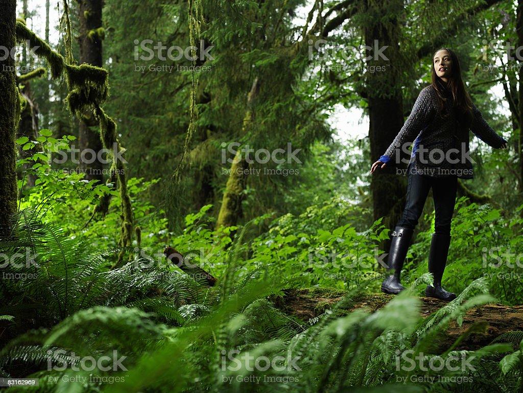 Portrait of young woman balancing on fallen tree. royaltyfri bildbanksbilder