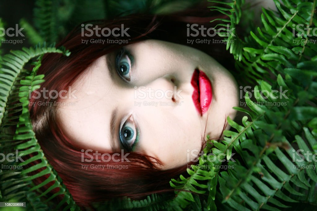 Portrait of Young Woman Behind Fern Leaves royalty-free stock photo