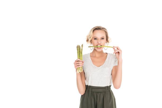 porträt der jungen frau beißen rohen spargel in händen - spargel vegan stock-fotos und bilder