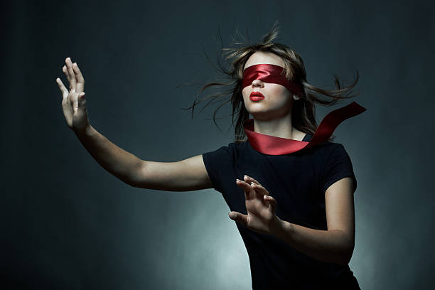 Portrait of young woman blindfolded with silky red cloth stock photo