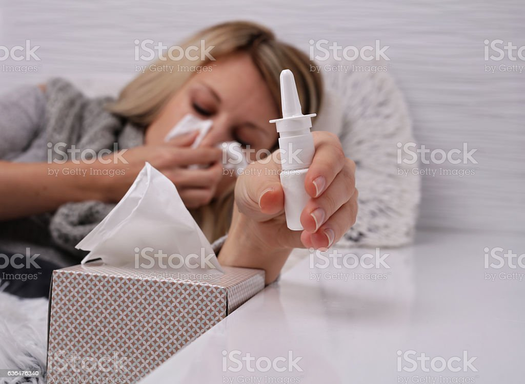 Portrait of young woman blowing nose and holding nasal spra stock photo
