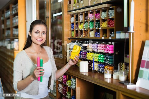 Portrait of young glad woman choosing candles in art shop