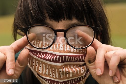 Portrait of Young Woman Cleaning her Glasses from Fog when wearing Protective Mask