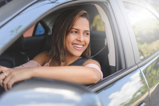 Portrait of young woman driving a car stock photo
