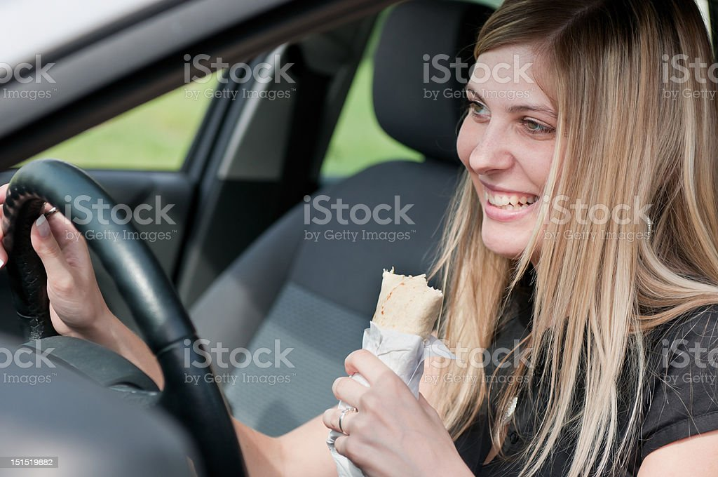 Portrait of young woman eating while driving car royalty-free stock photo