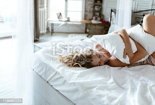 Portrait of young woman enjoying time in bed