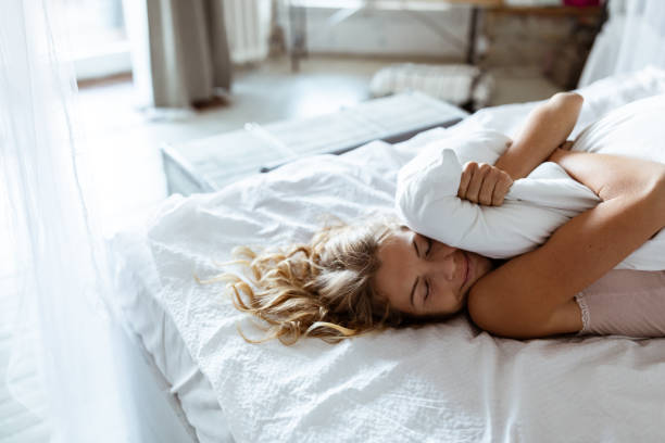 Portrait of young woman enjoying time in bed stock photo