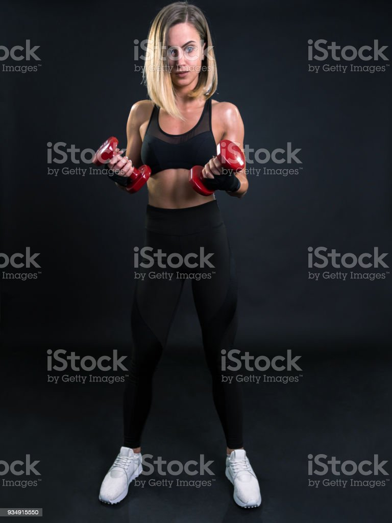 Portrait of young woman fitness coach holding dumbbells and looking at camera stock photo