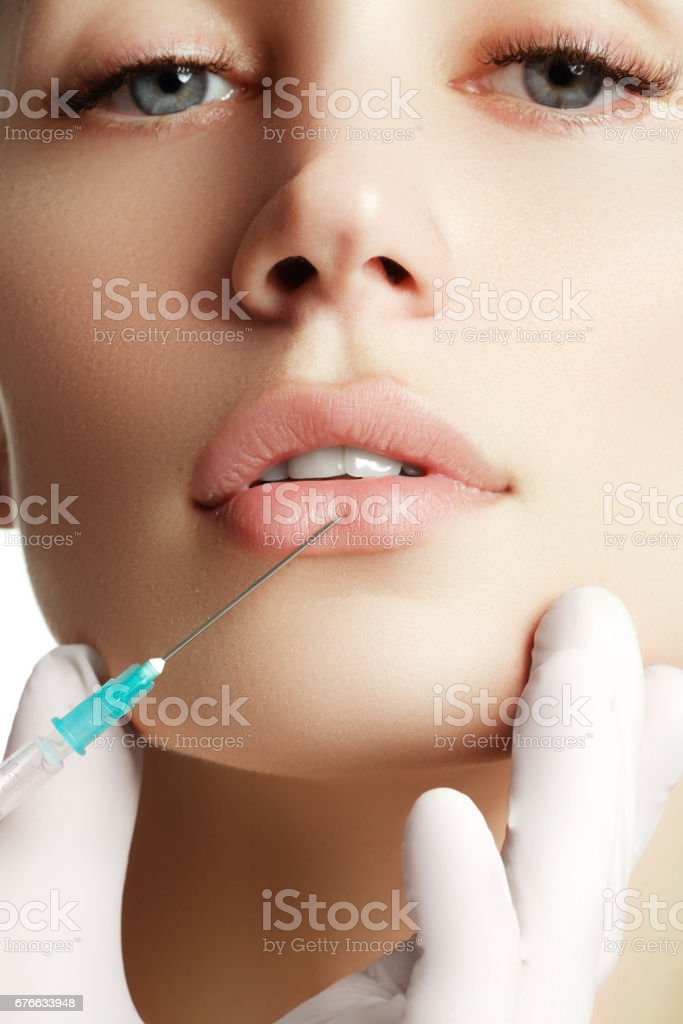 Portrait of young  woman getting cosmetic injection. Closeup of stock photo