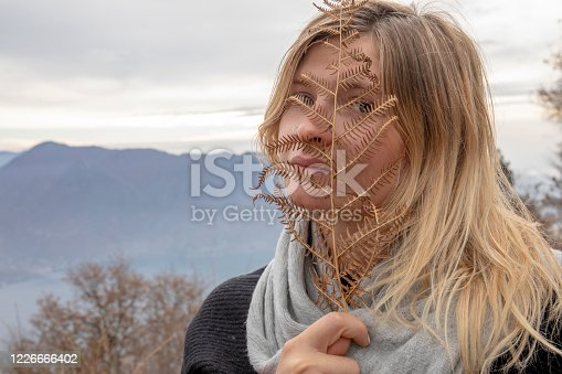 The sun rises behind her in the mountains and lake