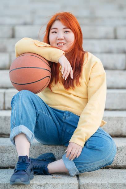 バスケットボールをし、階段で座っている若い女性の肖像 - real bodies ストックフォトと画像